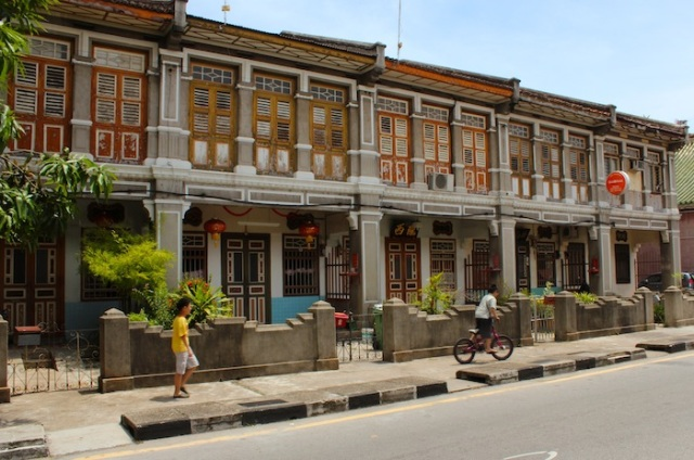 Ochre tones of a row of colonial era shophouses with local boys heading home. Armenian Street.