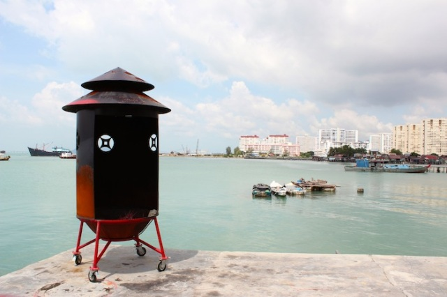 Red and bronze sacrificial drum perched at the very edge of the Chew Clan Jetty, with modern Penang in the near distance.