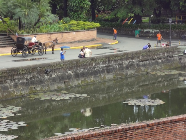 A traditional calesa and domestic tourists, just outside Fort Santiago.