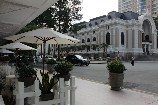 Across from the Eden Center sits the Hotel Continental (1880).  This is the view from its famous terrace (in the foreground), where countless writers and journalists have installed themselves, in order to observe the city's comings and goings. In the background sits the restored Opera House, previously the Vietnam National Assembly, and now the Municipal Theatre.