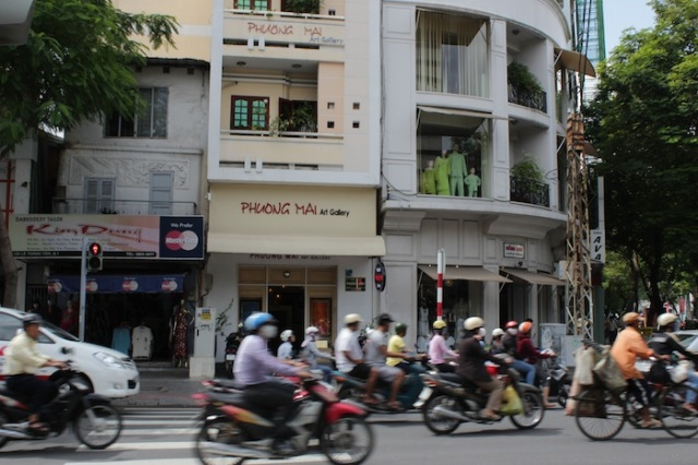 Motorcycles zooming past the Phuong Mai Art Gallery.