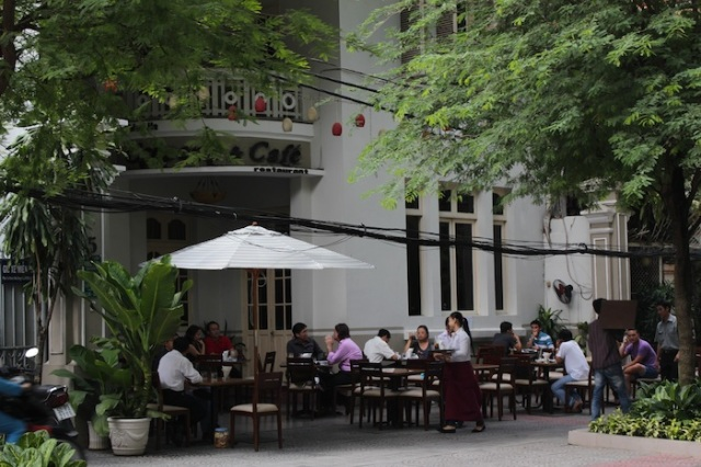 Locals enjoying crepes and coffee at a popular café, housed in a lovely French colonial villa near the Reunification Palace.