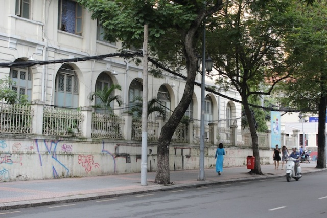 Glimpse of an ao dai on Dong Khoi Street. The building to the left is part of the original French infantry barracks.