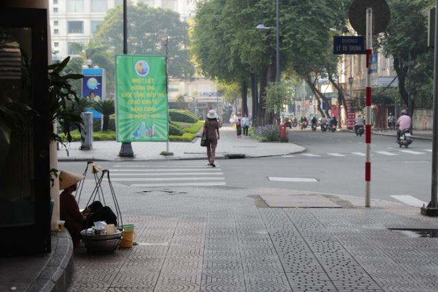 A streetfood vendor in traditional garb sits on Dong Khoi Street, contemplating what Saigon has become. To the left are the Vincom Towers.