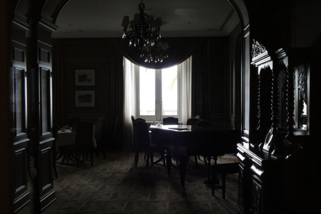 A ghostly 1885 Restaurant, viewed through a small glass panel in its door.