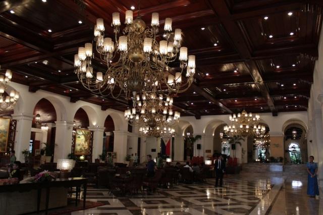 The vast, opulent lobby of the Manila Hotel.