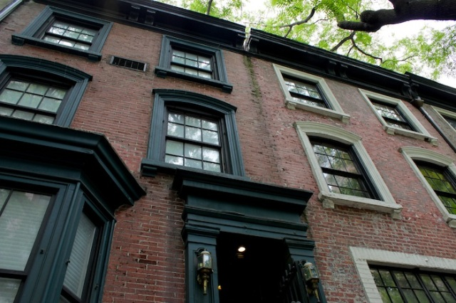 38 – No. 124: A red brick townhouse with green awnings.