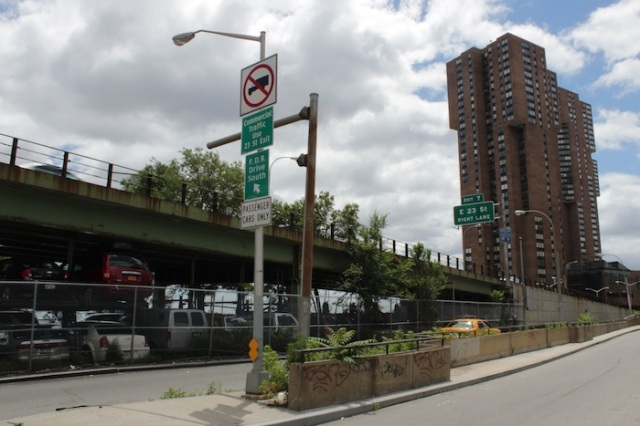 50 – The rust-streaked hulk of the FDR Drive Elevated Highway. Beneath it, a makeshift parking garage. To the right, another dystopian, brutalist apartment block.