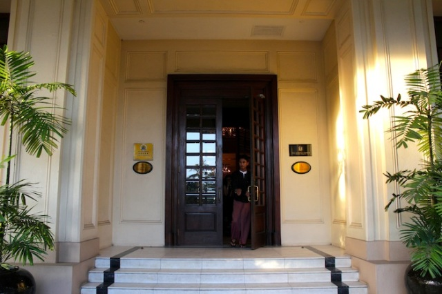 Entrance to the hotel, and longyi-clad doorman.