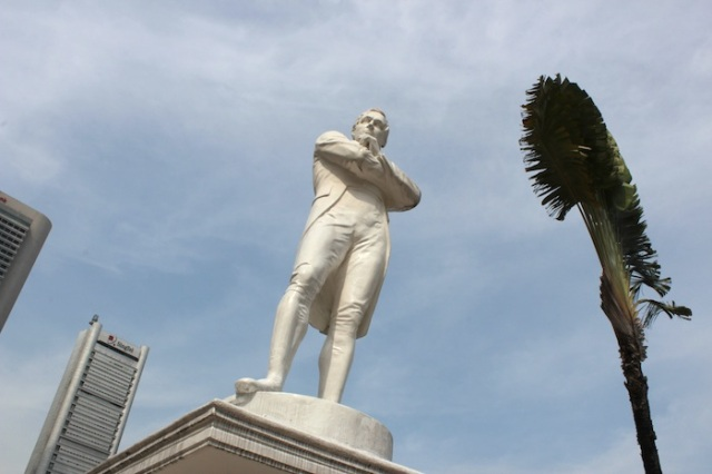 In a pensive mood, with his colonial capital behind him, and a traveller's palm to keep him cool.