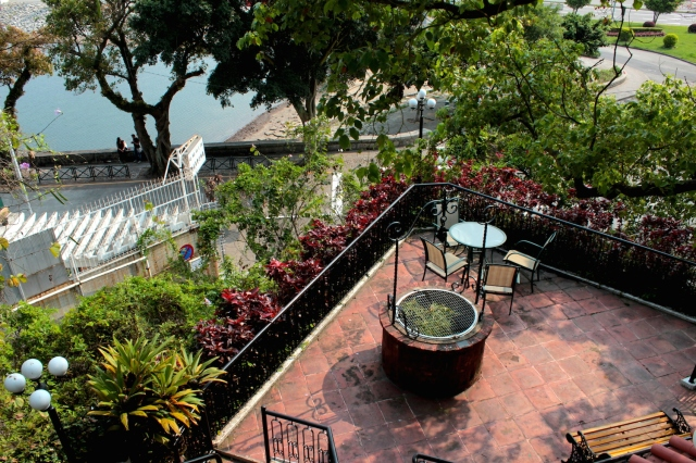 From the swimming pool, looking down upon the ancient, disused well, and further down upon a courting couple along the Avenida da Republica and West Bay Lake.