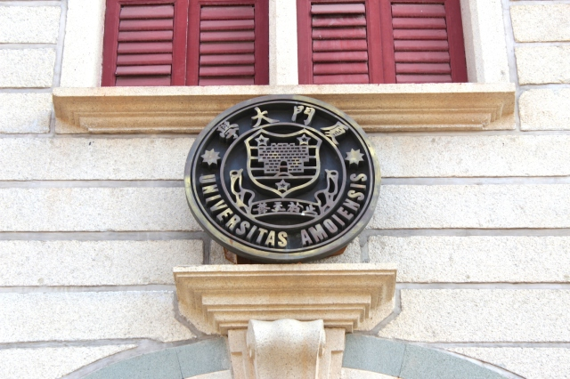"The university crest reads ""Universitas Amoiensis,"" referencing the older name of Xiamen."