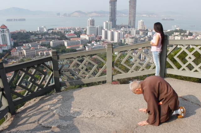 A pious monk genuflecting and giving thanks on Mount Putuo.