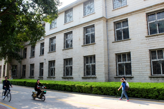 Students leisurely cycling along another campus building from the 1930s.