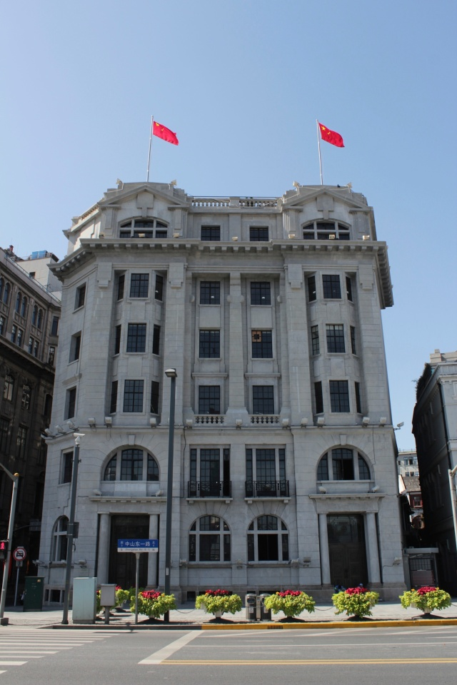 Bund #5 is the Nisshin Kisen Kaisha (Japanese Steamship Company) Building, designed by Lester Johnson & Morris in a Beaux-Arts style and erected in 1921.  It was restored and reopened in 1999 as M on the Bund.