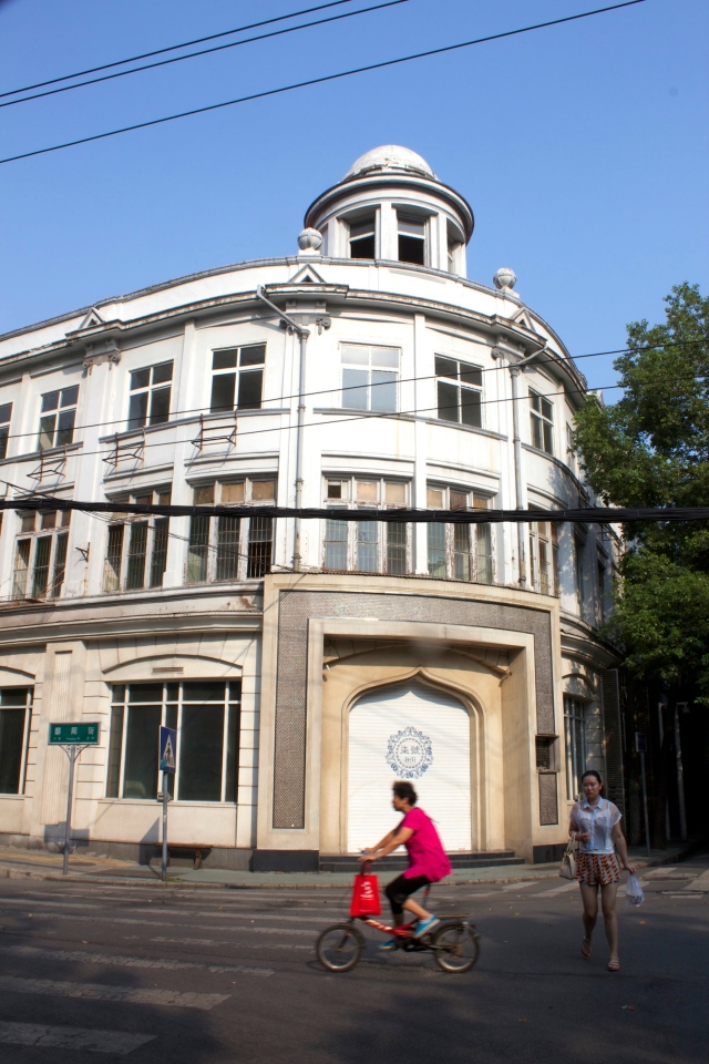 A lady cycles past a building at the intersection of the Russian and French concessions.