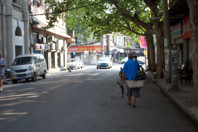An old fisherman walks down the street hawking a live paddlefish from the Yangtze River.