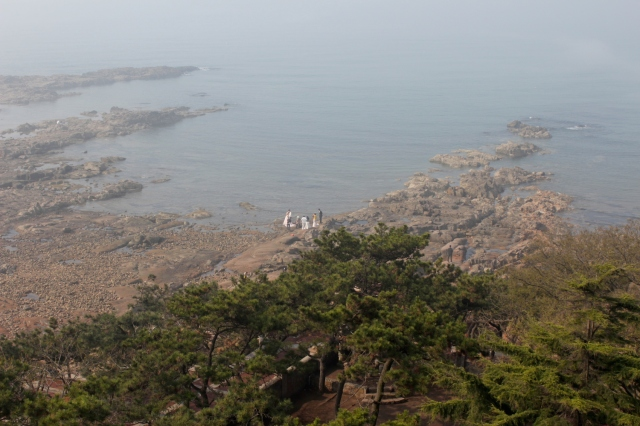 View from the Tower of a wedding photoshoot on the rocky coastline.