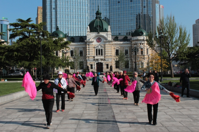Chinese seniors dancing in what was Nicholas Square.  the building was built in 1910 during the Japanese era and housed the Daqing Bank.