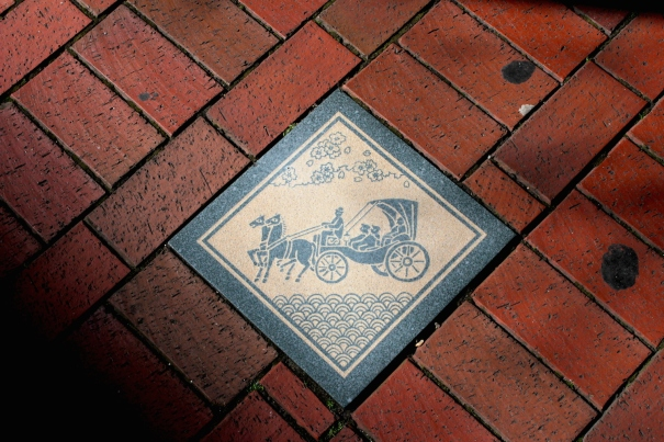 Street tile depicting a horse carriage on Bashamichi.